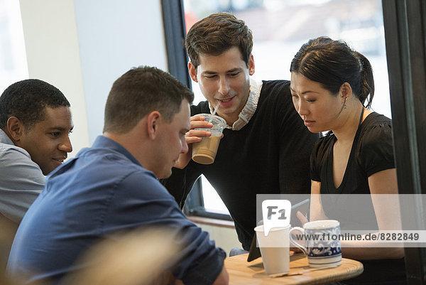 Eine Gruppe von Menschen  die um einen Tisch in einem Coffee Shop sitzen. Sie schauen auf den Bildschirm eines digitalen Tabletts. Drei Männer und eine Frau.
