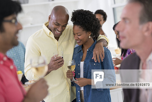 Networking Party Or Informal Event. A Man And Woman  With A Crowd Around Them.