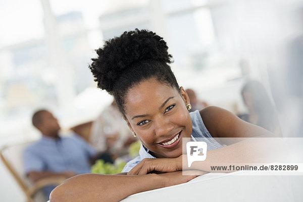 Büro. Eine junge Frau  die breit lächelt.