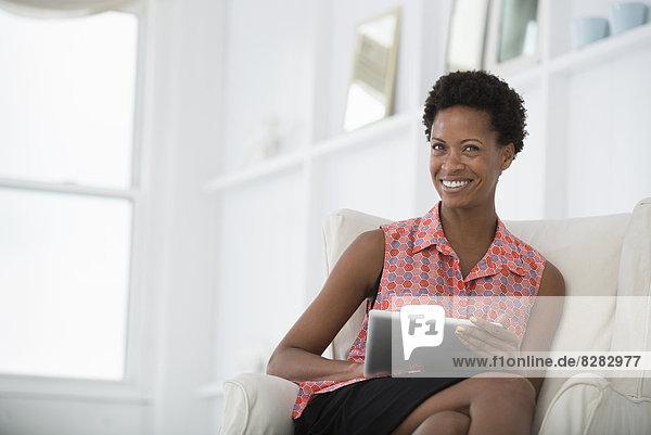 Büroleben. Eine Frau sitzt auf einem Sofa und benutzt ein digitales Tablet.