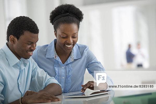 Innenministerium. Ein Mann und eine Frau  die Seite an Seite sitzen und ein digitales Tablet benutzen.