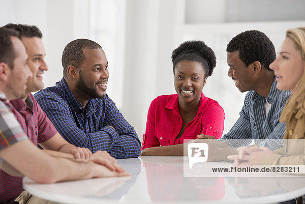 Büro. Eine Gruppe von vier Personen  zwei Männer und zwei Frauen sitzen und reden miteinander.