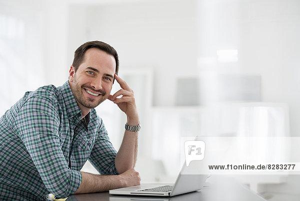 Innenministerium. Ein Mann  der an einem Tisch sitzt und einen Laptop-Computer benutzt.