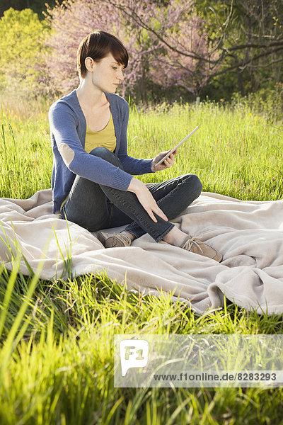 sitzend junge Frau junge Frauen sehen halten Feld Tablet PC Außenaufnahme sichtschutz