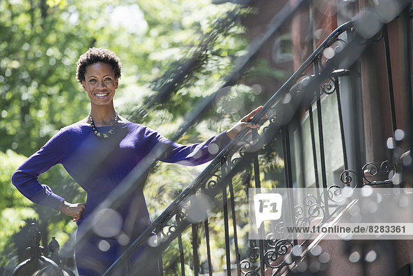 Stadt. Eine Frau in einem violetten Kleid  die auf den Stufen vor einem Stadthaus steht.
