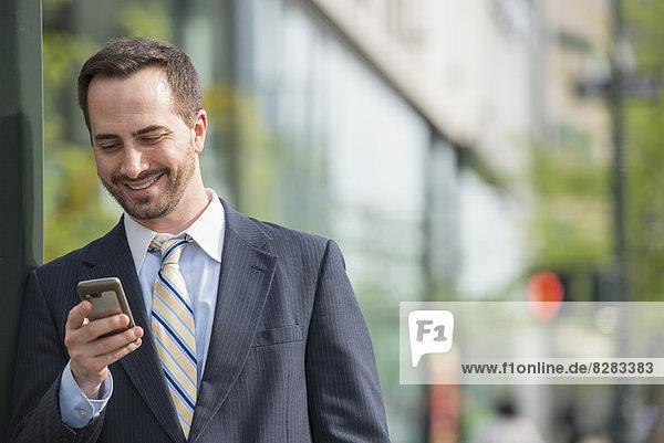 Stadt. Ein Mann im Geschäftsanzug,  der seine Nachrichten auf seinem Smartphone abruft.