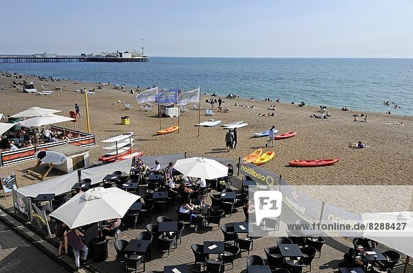 View down over beach side cafes to Brighton beach to Pier Brighton East Sussex England.