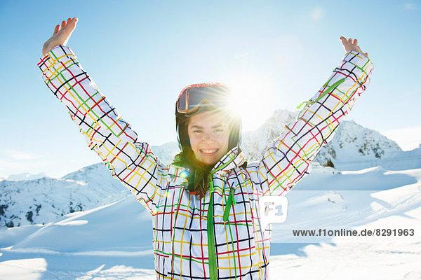 Porträt einer jungen Skifahrerin mit ausgestreckten Armen  Les Arcs  Haute-Savoie  Frankreich Porträt einer jungen Skifahrerin mit ausgestreckten Armen, Les Arcs, Haute-Savoie, Frankreich
