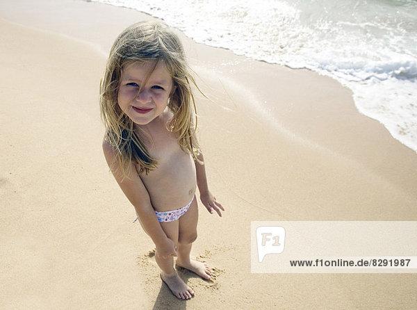 Mädchen posiert für Kamera am Strand
