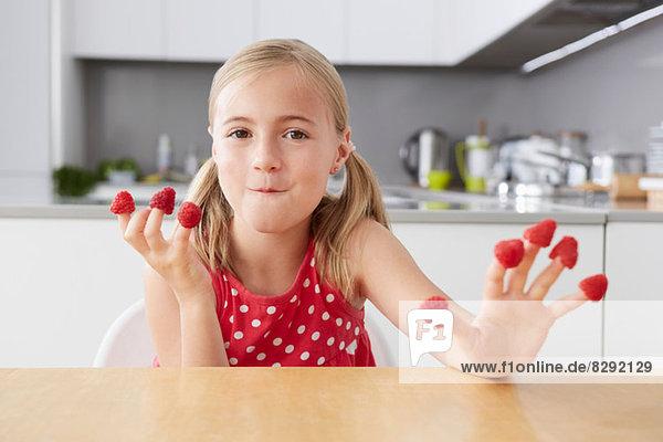 Mädchen isst Himbeeren aus den Fingern
