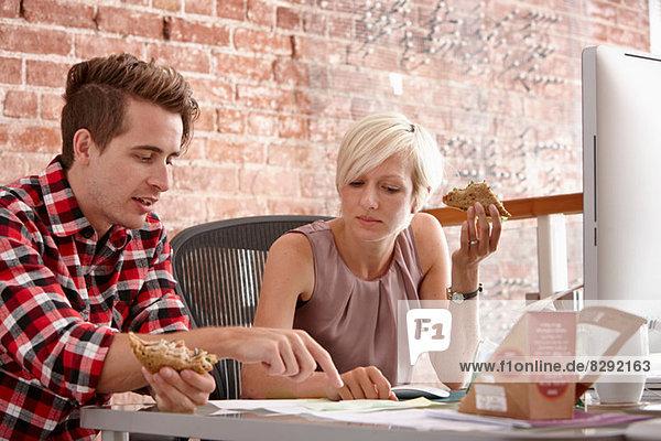 Zwei Kollegen essen Sandwiches am Schreibtisch