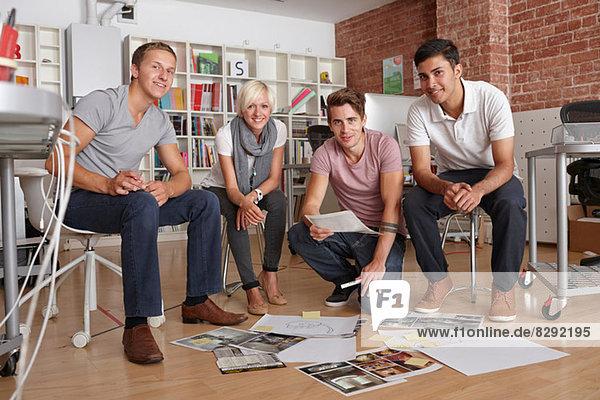 Portrait von Kollegen mit Papieren auf dem Boden