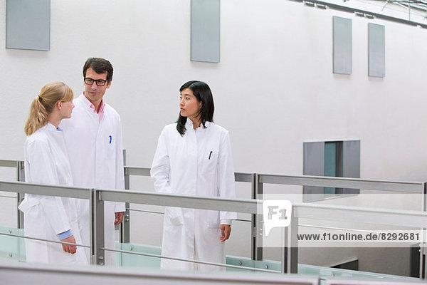 Gruppe von Wissenschaftlern im Atrium im Gespräch