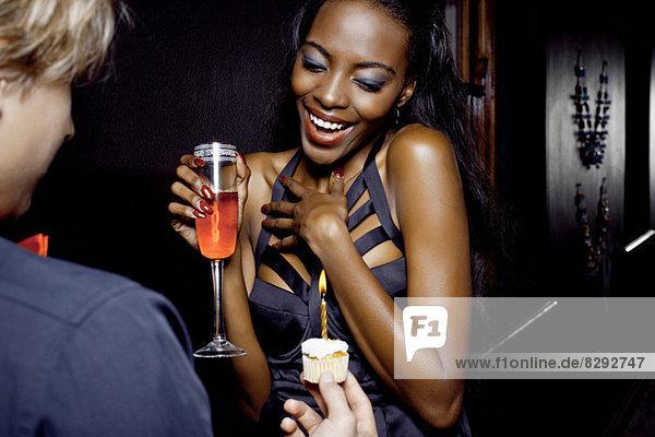 Junge Frau bekommt Geburtstagskuchen im Nachtclub