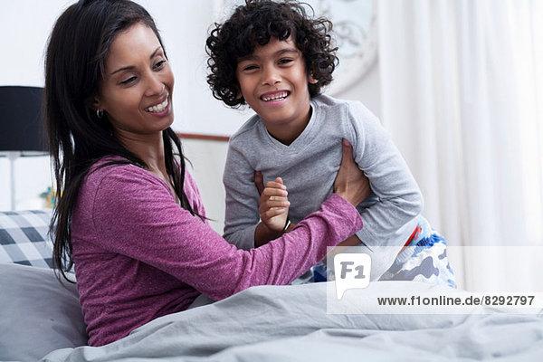 Sohn und Mutter im Bett  lächelnd