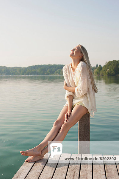 Young woman sitting on pier post