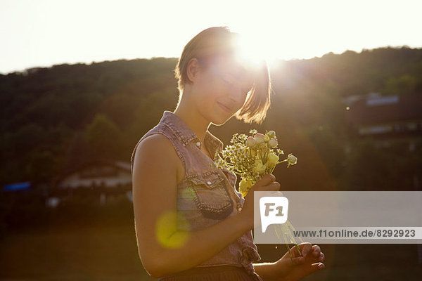 Young woman in meadow holding bunch of wild flowers