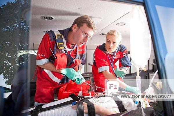 Rettungssanitäter bei der Arbeit am Patienten im Krankenwagen