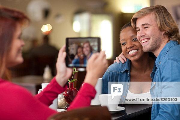 Gruppe von Freunden im Cafe mit digitalem Tablett