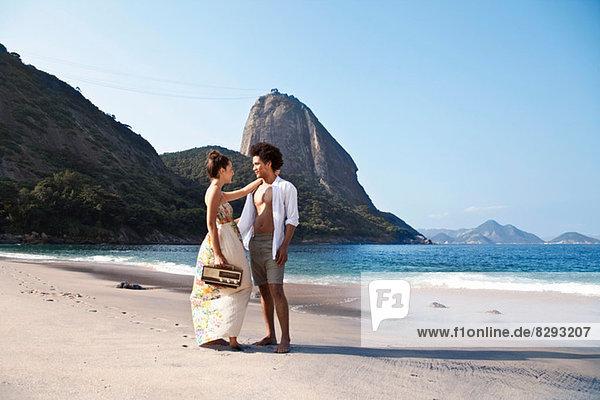 Couple on beach with radio  Rio de Janeiro  Brazil