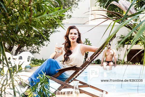 Young woman on sunlounger by swimming pool with drink
