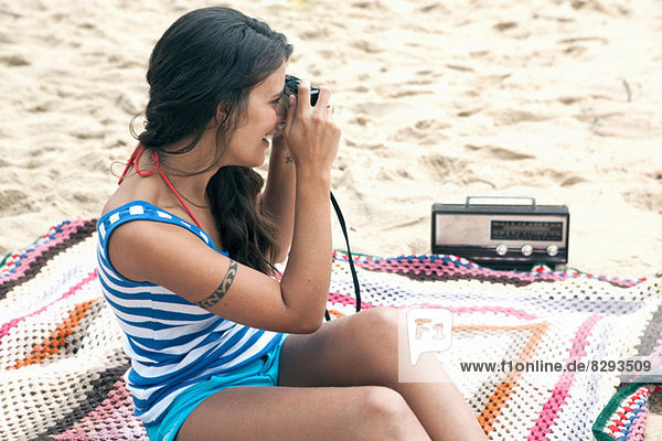 Woman on blanket on beach using camera