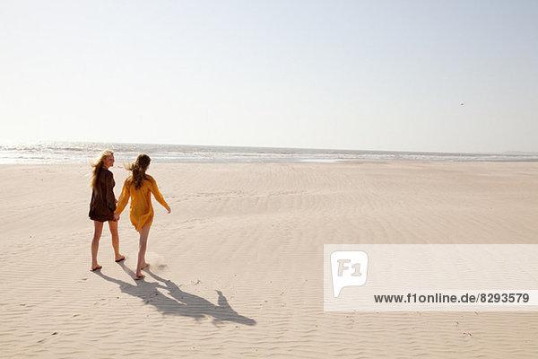 Mutter und Tochter beim Spaziergang am Strand