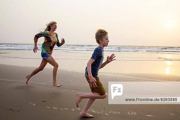Mutter und Sohn beim Laufen am Strand