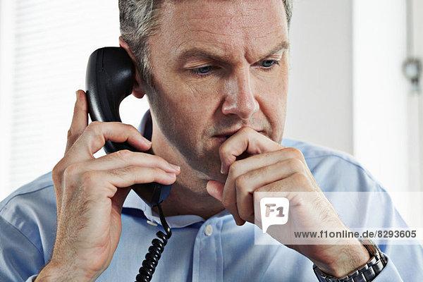 Reife Geschäftsleute am Festnetztelefon