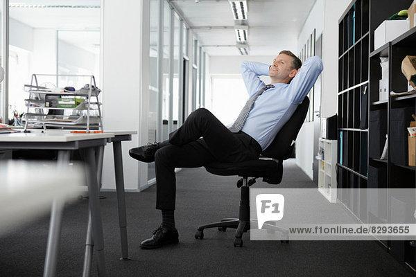 Ein reifer Geschäftsmann  der sich im Bürostuhl zurücklehnt.