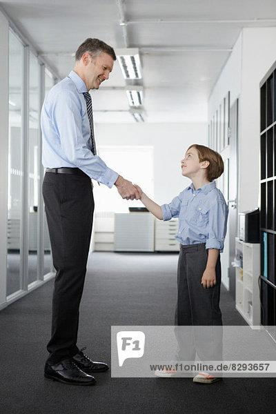 Vater und Sohn beim Händeschütteln im Amt