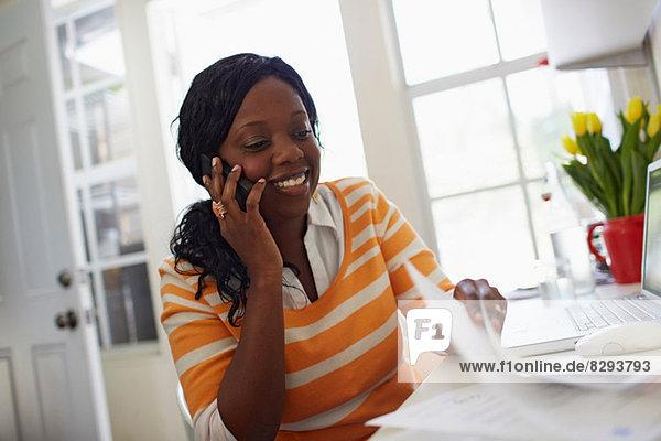Frau telefoniert und schaut sich den Papierkram an.