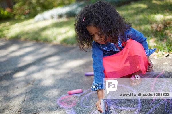 Mädchenzeichnung mit Kreide auf dem Bürgersteig