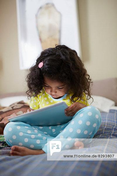 Kind auf dem Bett sitzend mit digitalem Tablett