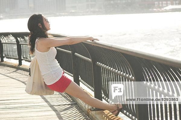 Junge Frau lehnt sich auf Geländer zurück und schaut auf den Fluss.
