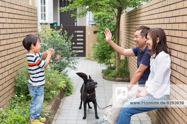 Familie mit Hund  Vater winkt dem Sohn zu