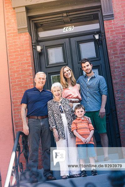 Porträt der Drei-Generationen-Familie vor der Haustür