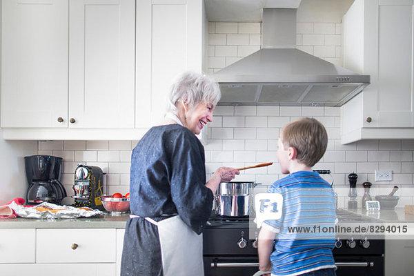 Großmutter und Enkel bereiten das Essen zu Hause zu.