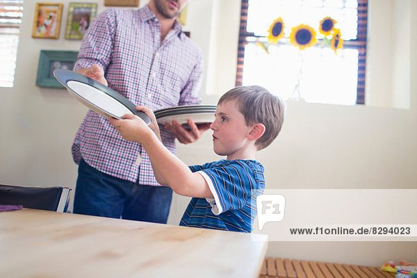 Son setting the table with father