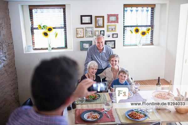 Mann fotografiert Familie beim Essen