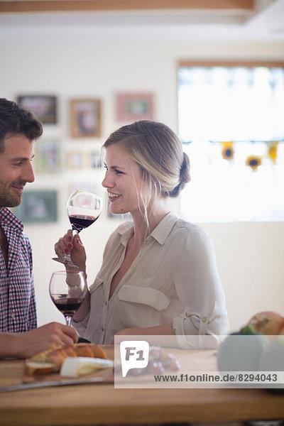 Paar trinkt Rotwein am Esstisch