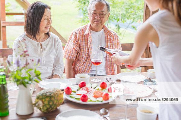 Frau serviert den Eltern Wein am Esstisch