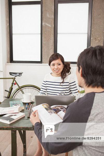 Junges Paar am Tisch sitzend mit Computer und Zeitschrift