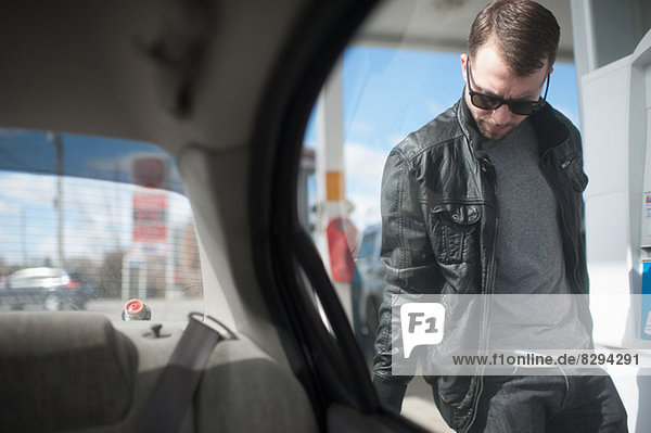 Young man putting fuel in car  view from vehicle interior