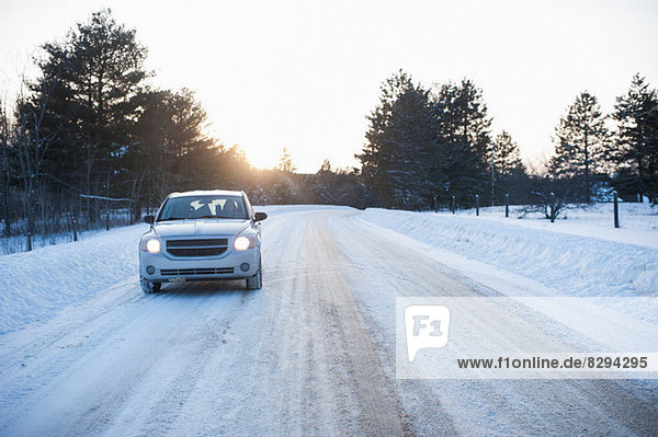 Car driving along road in snow