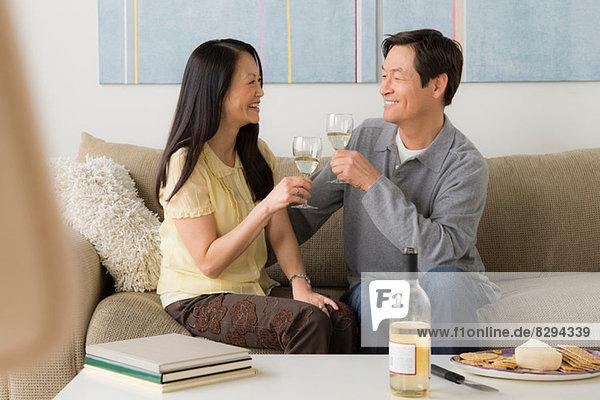 Reife Paare sitzen auf dem Sofa und rösten Weißwein.