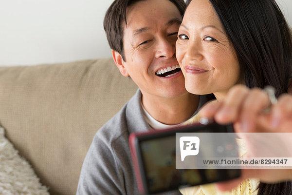 Reife Paare fotografieren sich selbst mit Digitalkamera