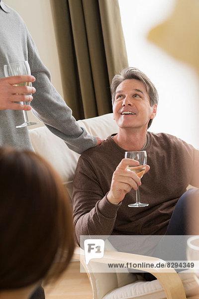 Reife Freunde treffen sich mit Weißwein