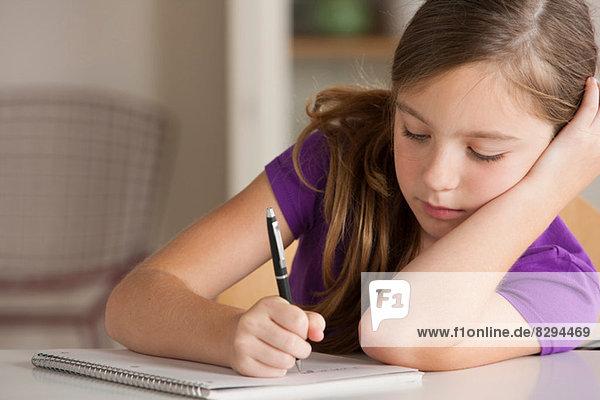 Mädchen schreiben im Notizbuch
