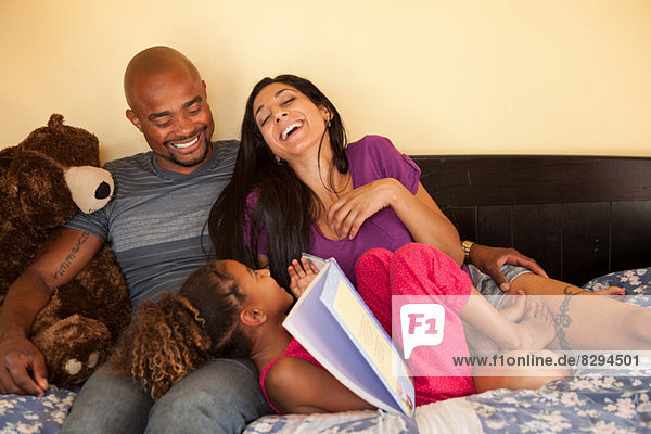 Mother and father with daughter on sofa  laughing